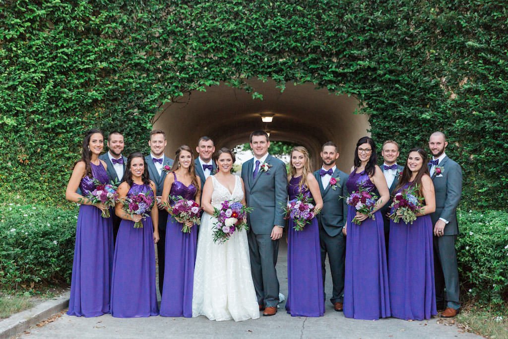 Outdoor Garden Wedding Party Portrait, Bride in Calla Blanch V Neck Wedding Dress, Bridesmaids in Jasmine B2 Sequin Violet Dresses, Groom and Groomsmen in Gray Suits with Purple Bow Ties, with White, Magenta, Lavender Purple Bouquets with Greenery   Tampa Bay Outdoor Wedding Venue Lakewood Ranch Golf & Country Club