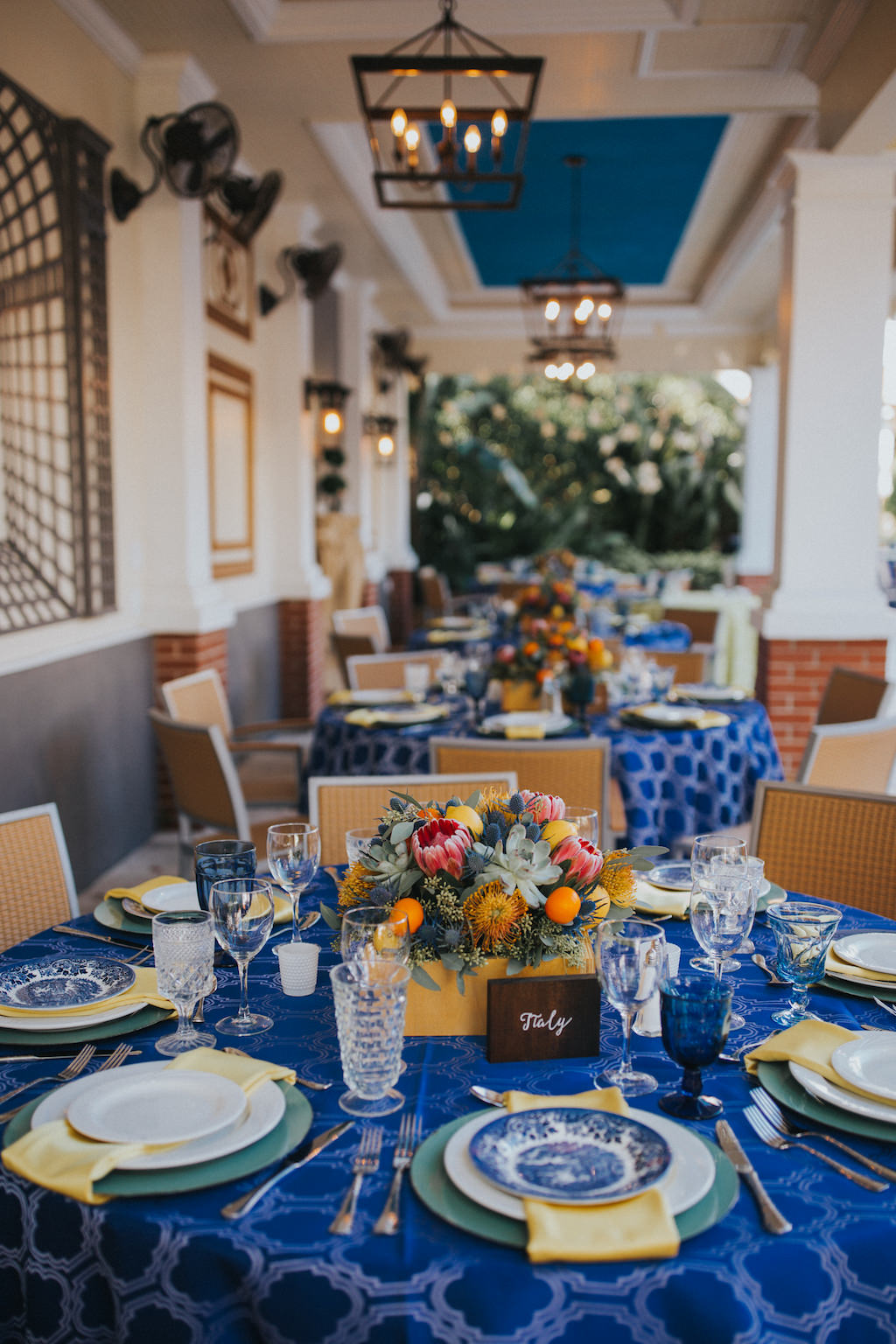 Mediterranean Inspired Wedding Reception Round Table Decor with Low Yellow, Orange, Pink and Succulent Greenery Centerpiece, Wooden Table Number European Country Names Sign with White Script, Sage Green Chargers and Yellow Napkins, Cobalt Blue Patterned Tablecloth, and Blue Painted China Plates | Sarasota Wedding Planner Jennifer Matteo Event Planning | Over the Top Rental Linens