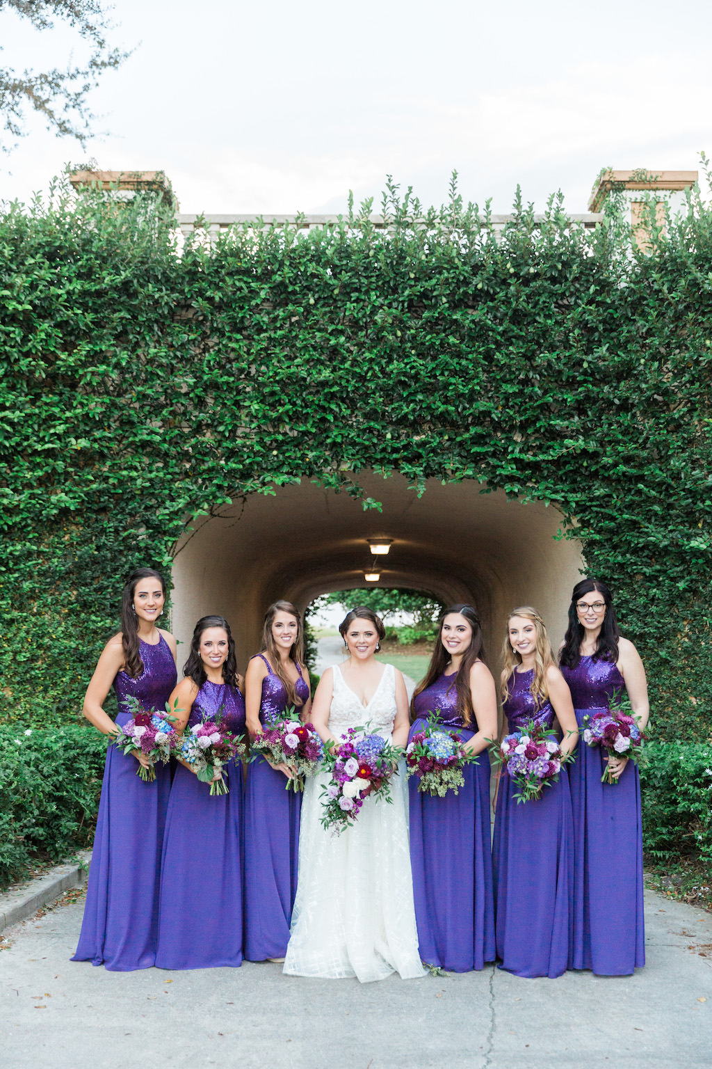 Outdoor Garden Wedding Party Portrait, Bride in Calla Blanch V Neck Wedding Dress, Bridesmaids in Jasmine B2 Sequin Violet Dresses, with White, Magenta, Lavender Purple Bouquets with Greenery   Tampa Bay Outdoor Wedding Venue Lakewood Ranch Golf & Country Club