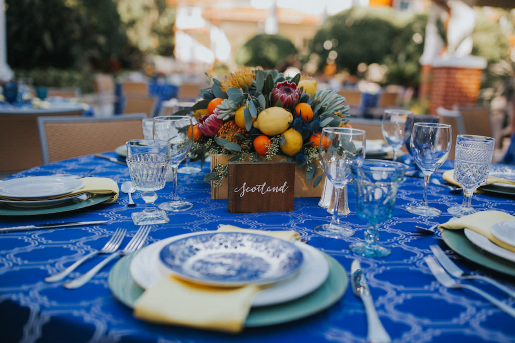 Mediterranean Inspired Wedding Reception Round Table Decor with Low Yellow, Orange, Red and Succulent Greenery Centerpiece with Lemons and Persimmon, Wooden Table Number European Country Names Sign with White Script, Sage Green Chargers and Yellow Napkins, Cobalt Blue Patterned Tablecloth, and Blue Painted China Plates | Sarasota Wedding Planner Jennifer Matteo Event Planning | Over the Top Rental Linens