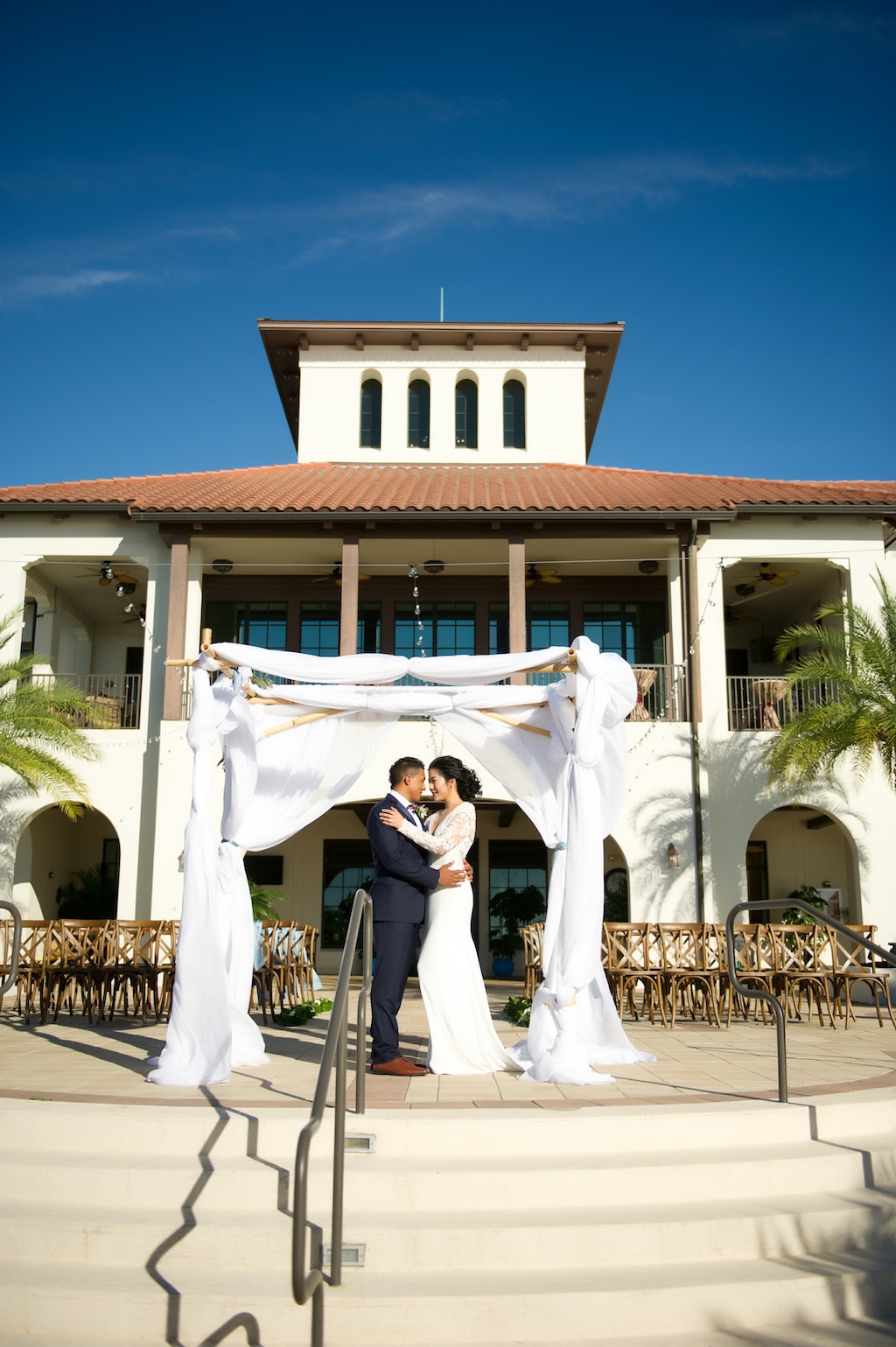 Outdoor Waterside Wedding Ceremony Portrait, Bride and Groom Under White Draped Ceremony Arch | Tampa Bay Waterfront Wedding Ceremony Venue Westshore Yacht Club