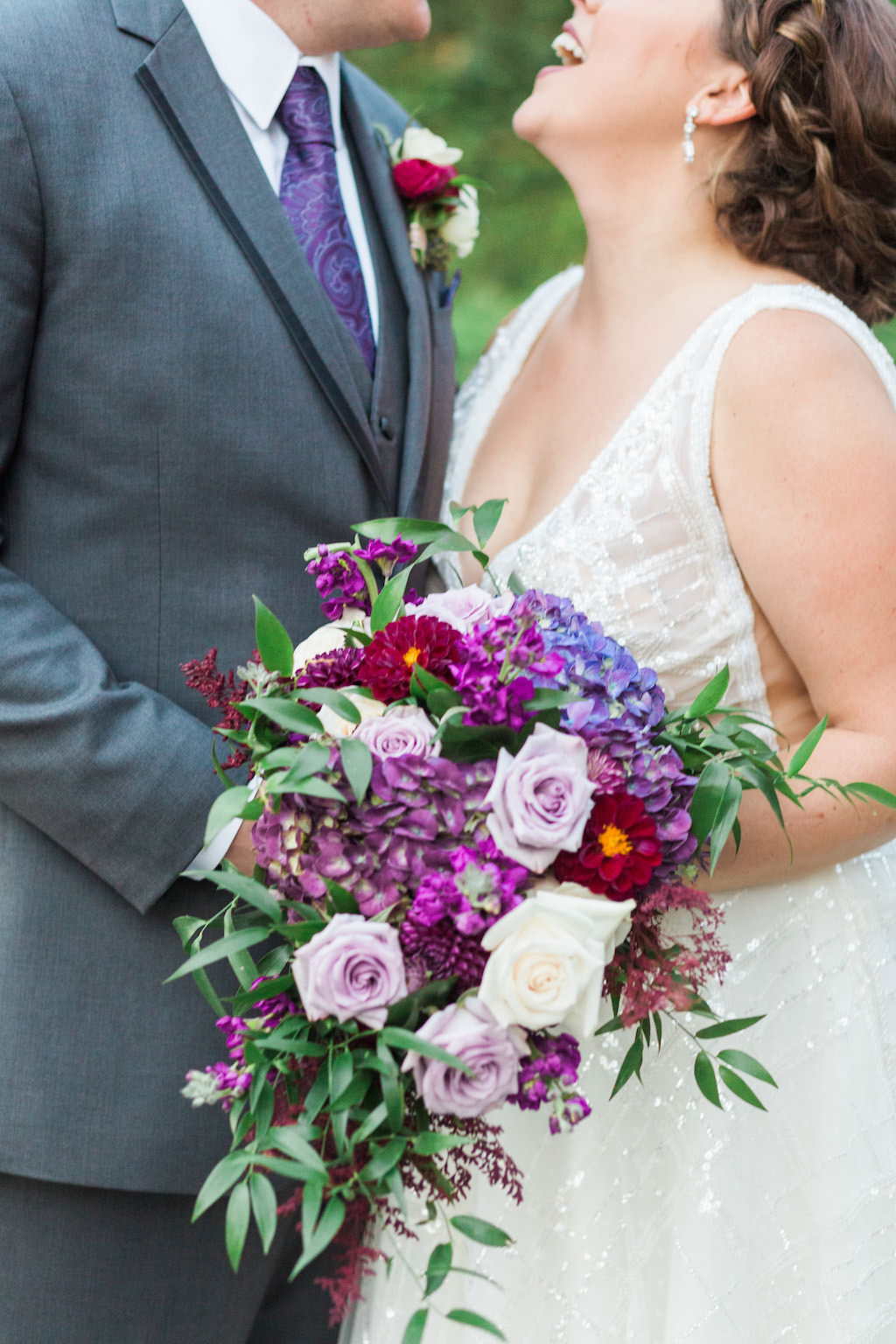 Outdoor Garden Bride and Groom Wedding Portrait with Magenta, Lavender, Violet, and Purple Bouquet with Greenery, Groom in Gray Suit with Paisley Purple Tie and White and Pink Boutonniere
