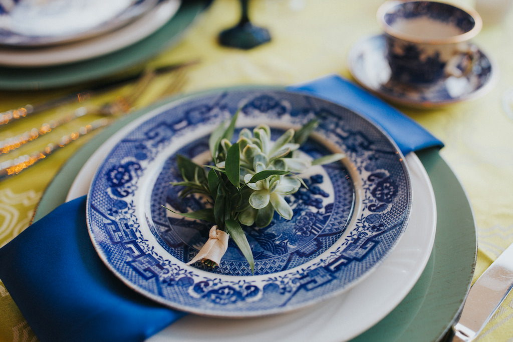 Mediterranean Sage Green and Cobalt Blue Wedding Reception Table Place Setting with Succulent Greenery Bundle, Blue Painted China, Green Charger and Blue Napkin with Blue Painted China Teacup | Sarasota Wedding Planner Jennifer Matteo Event Planning