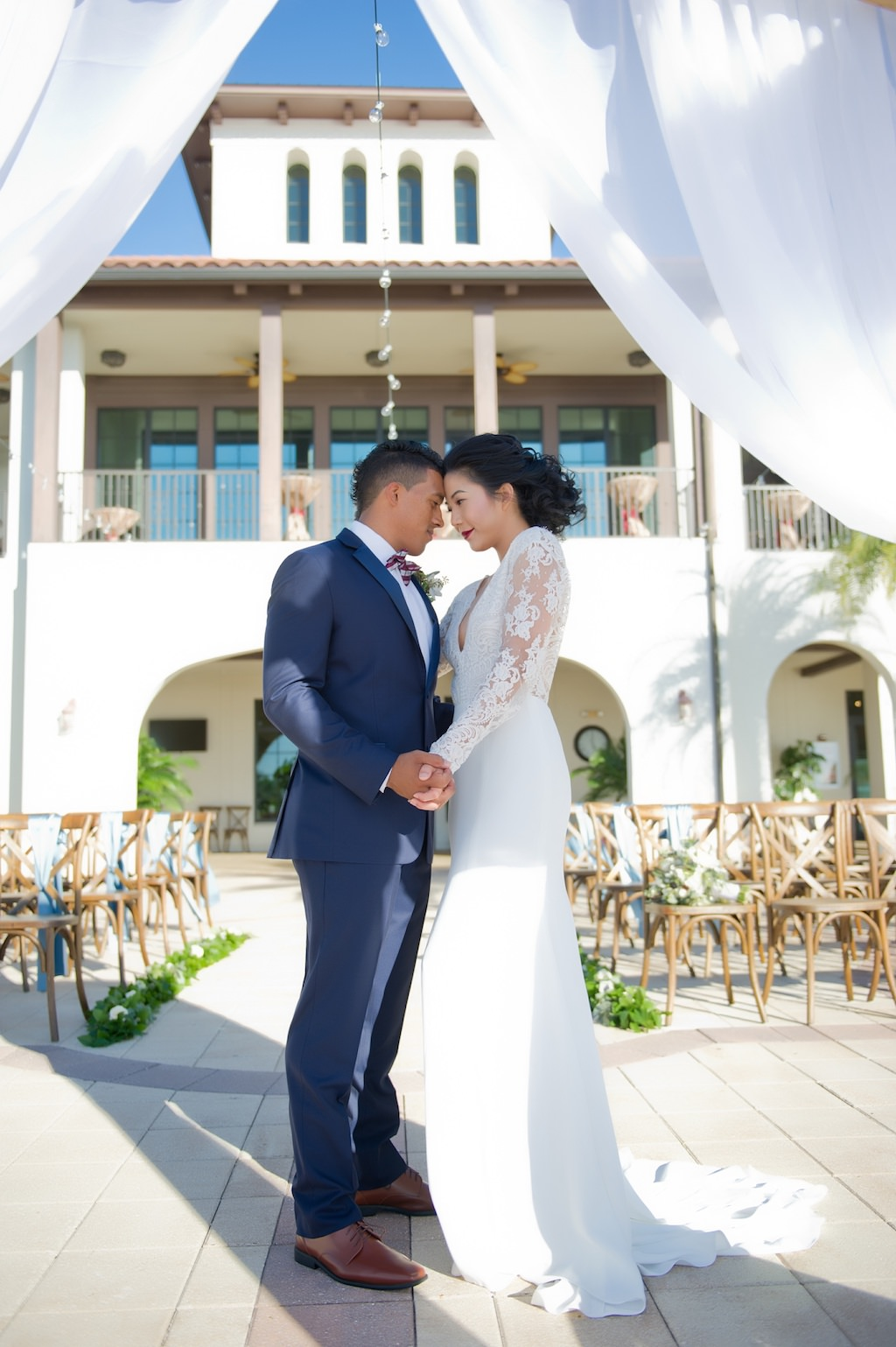 Outdoor Waterside Wedding Ceremony Portrait, Bride and Groom Under White Draped Ceremony Arch | Tampa Bay Waterfront Wedding Ceremony Venue Westshore Yacht Club | Tampa Bay Wedding Photographer Andi Diamond Photography