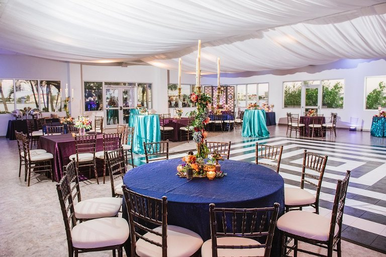 Whimsical Jewel Tone Wedding Reception with Amethyst, Midnight, and Emerald Linens, and Tall Candelabra with Hanging Flowers and Greenery Centerpiece and White Ceiling Draping and Wooden Chiavari Chairs | Tampa Bay Wedding Rentals Over the Top Linens | Clearwater Wedding Planner Special Moments Events Planning | Indoor and Outdoor Wedding Waterfront Reception Venue Clearwater Beach Recreation Center