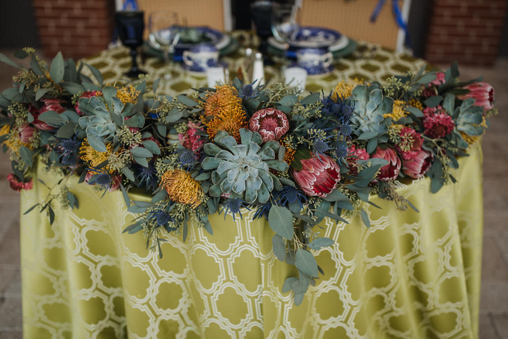 Mediterranean Inspired Wedding Reception Round Sweetheart Table with Low Succulent, Pink and Yellow Floral and Greenery Centerpiece on Patterned Gold Tablecloth | Over The Top Rental Linens | Sarasota Wedding Planner Jennifer Matteo Event Planning
