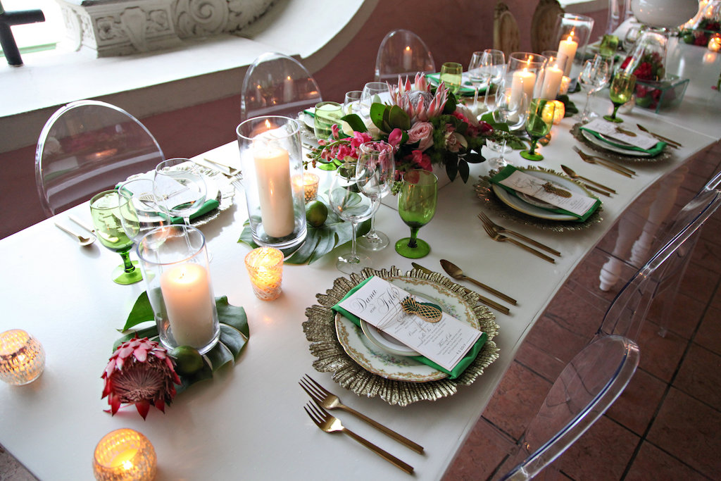 Old World Havana Inspired Wedding Reception Long White Curved Feasting Table with Pillar Candles on Monsterra Palm Fronds with Protea, Green Satin LInens, Pink LIly and White Orchid Low Centerpiece in White Box, Gold Chargers with Vintage China Place Settings and Brushed Flatware, and Oval Backed Clear Acrylic Chairs   St Pete Wedding Rentals A Chair Affair