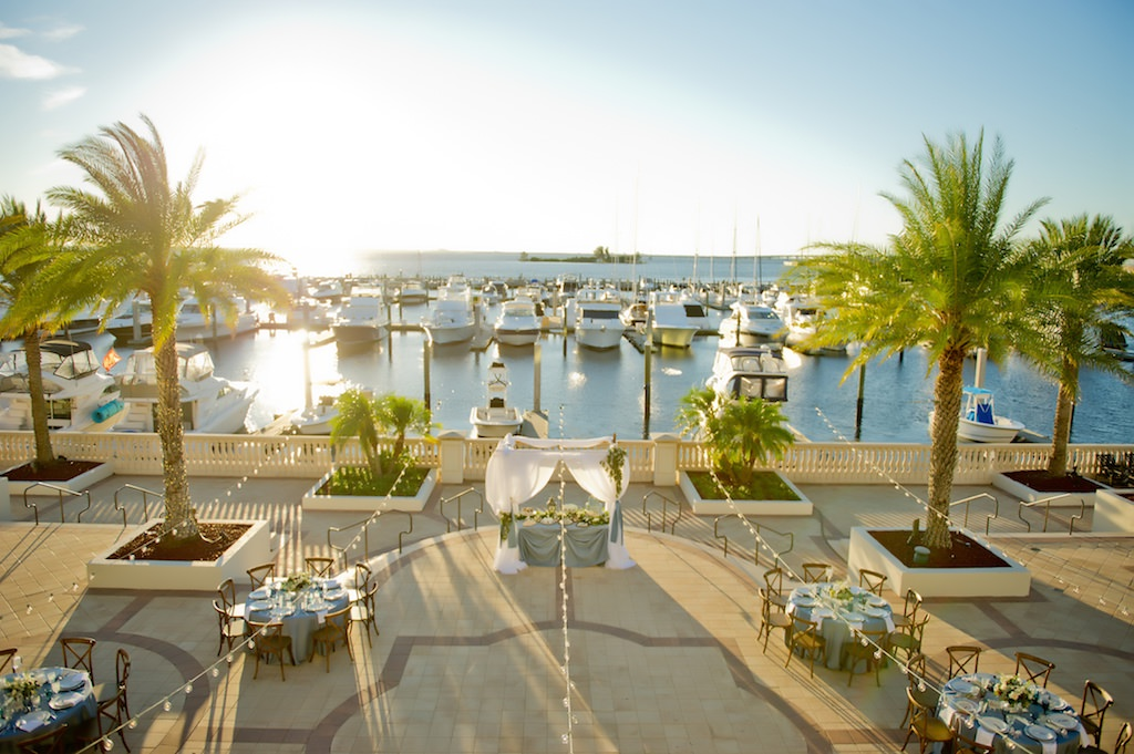 French Countryside Outdoor Waterfront Wedding Reception with Light Blue Linens, Wooden X Back Chairs, and Sweetheart Table under White Draped Arch with Greenery | Tampa Bay Wedding Planner Kelly Kennedy Weddings and Events | Tampa Waterfront Wedding Venue Westshore Yacht Club
