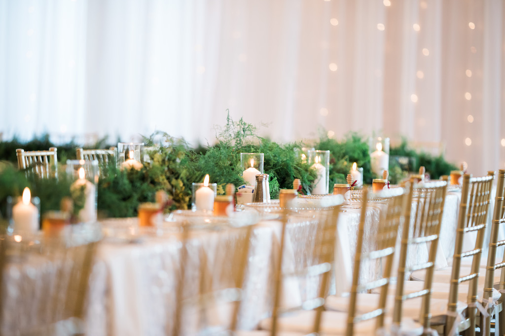 Whimsical Ballroom Wedding Reception Long Feasting Table Decor with Honey Jar Wedding Favors, Gold Chiavari Chairs, Pillar Candles in Glass Cylinder Vases, and Greenery Garland Runner Centerpiece