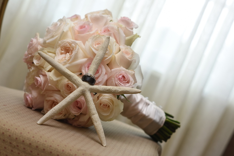 Blush Pink and Cream Rose Bouquet with White Ribbon and Groom's Black Wedding Band and Diamond Wedding Ring on Starfish