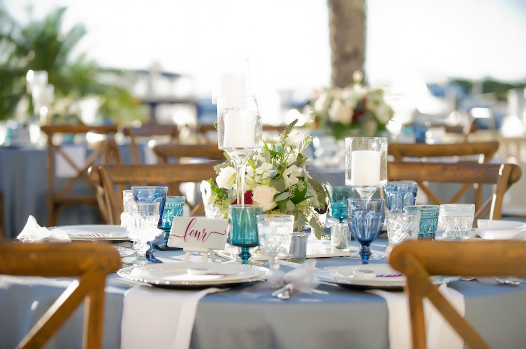 French Countryside Outdoor Wedding Reception Table Decor with Light Blue Linen, Blue Colored Drinking Glasses, Low White with Greenery and Red Rose Centerpiece, and Pillar Candles in Tall Glass Candleholders, with Stylish Pink Table Number on White Card | Tampa Wedding Planner Kelly Kennedy Weddings & Events | Tampa Bay Wedding Rentals Over The Top Linens and Events | Waterfront Tampa Wedding Reception Venue The Westshore Yacht Club