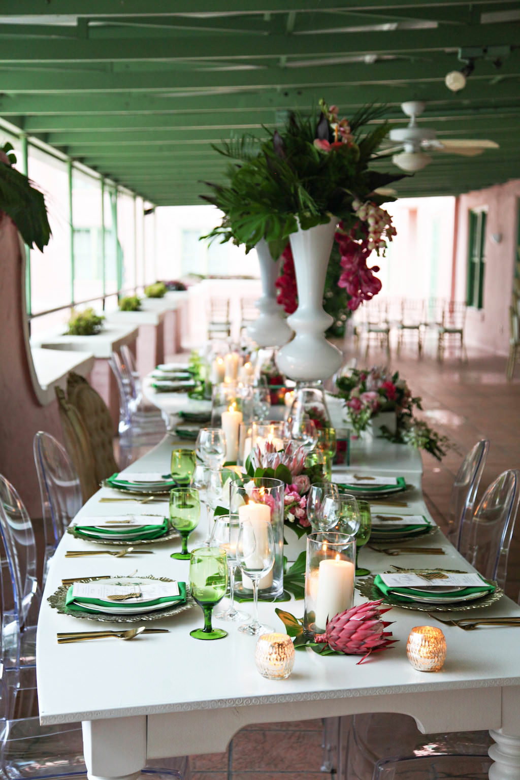 Outdoor Hotel Courtyard Old World Havana Inspired Wedding Reception with Long White Vintage Feasting Table with Clear Acrylic Oval Backed Chairs, Extra Tall Pink Orchid and Fern Greenery with Palm Fronds Centerpiece in White Vase, Low Centerpiece with Monsterra Palm Leaves and Florals in White Boxes, Colored Drinking Glasses and Green Satin Napkins, and Pillar Candles in Hurricane Votives   Tampa Bay Wedding Rentals A Chair Affair   St Pete Venue Vinoy Renaissance