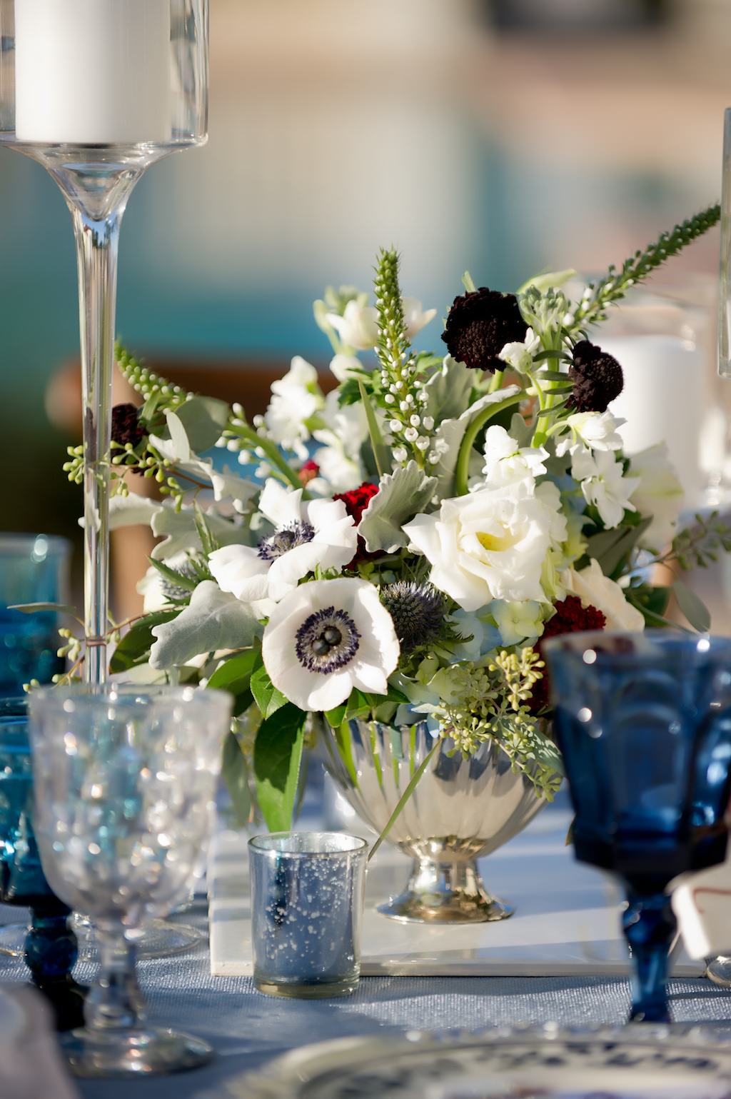 French Countryside Inspired Wedding Reception Table Decor with Low Anemone, Dark Red and Burgundy and White Flower Centerpiece with Greenery in Antique Silver Bowl Vase, with Blue Colored Drinking Glasses | Tampa Wedding Planner Kelly Kennedy Weddings and Events