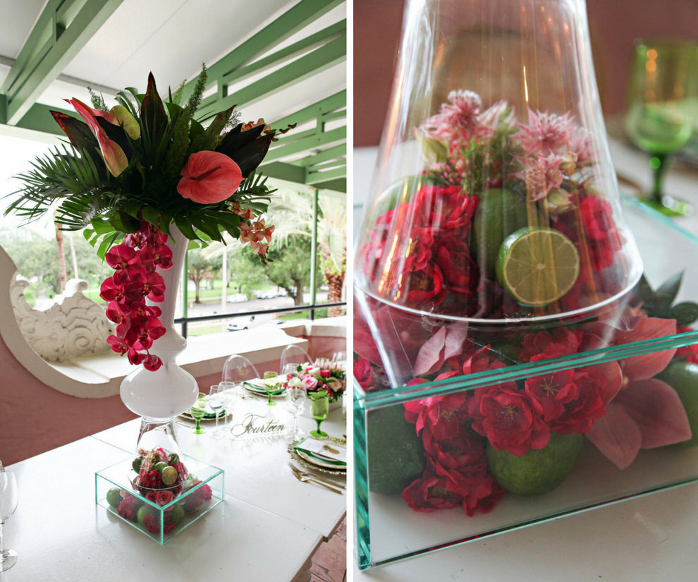 Hotel Courtyard Old World Havana Inspired Wedding Reception Extra Tall Centerpiece with Magenta Orchids and Pink Lilies, Tropical Fern and Palm Frond Greenery, in White Glass Vase on Clear Glass Vase Filled with Fruit, Limes and Florals