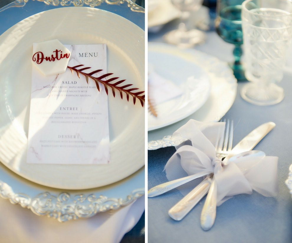 French Countryside Themed Wedding Reception Table Decor with Flatware in White RIbbon, and Burgundy Red Greenery on Pink Marble Printed Menu on Blue Linen | Tampa Wedding Papergoods A & P Designs | Tampa Bay Wedding Planner Kelly Kennedy Weddings & Events