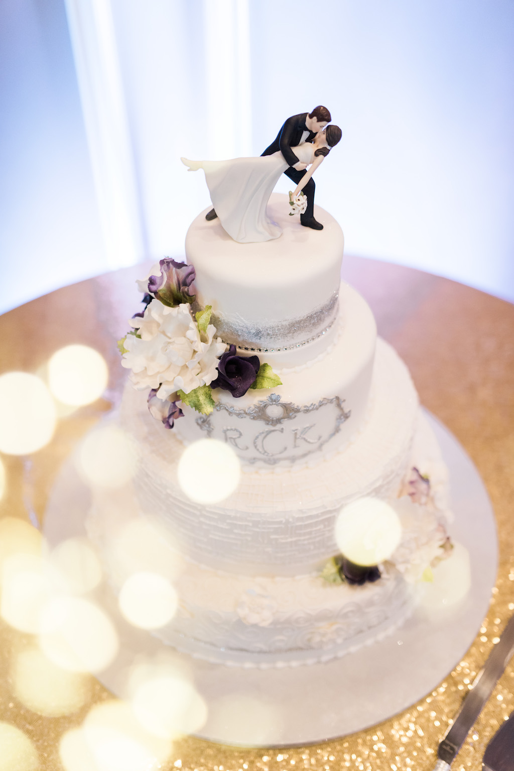 Four Tiered Round White Wedding Cake with Silver Decorative Icing, White and Purple Flowers, and Bride and Groom Figure Cake Topper