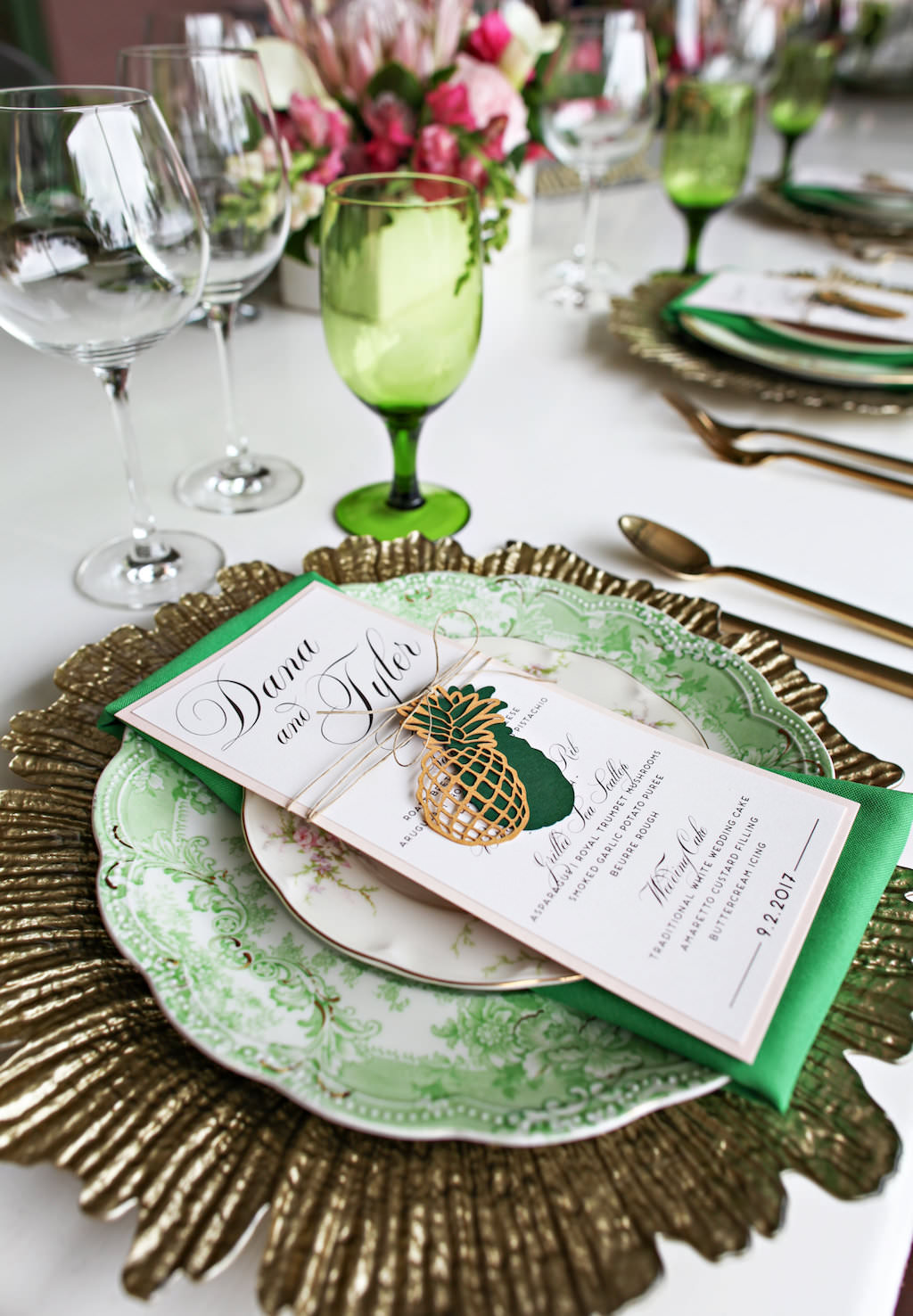 Old World Havana Tropical Inspired Wedding Reception Table Setting with Gold Charger, Vintage China Plates, Brushed Gold Flatware, Green Satin Linens and Laser-cut Pineapple Menu with Twine, and Colored Drinking Glasses   Tampa Bay Wedding Rentals A Chair Affair