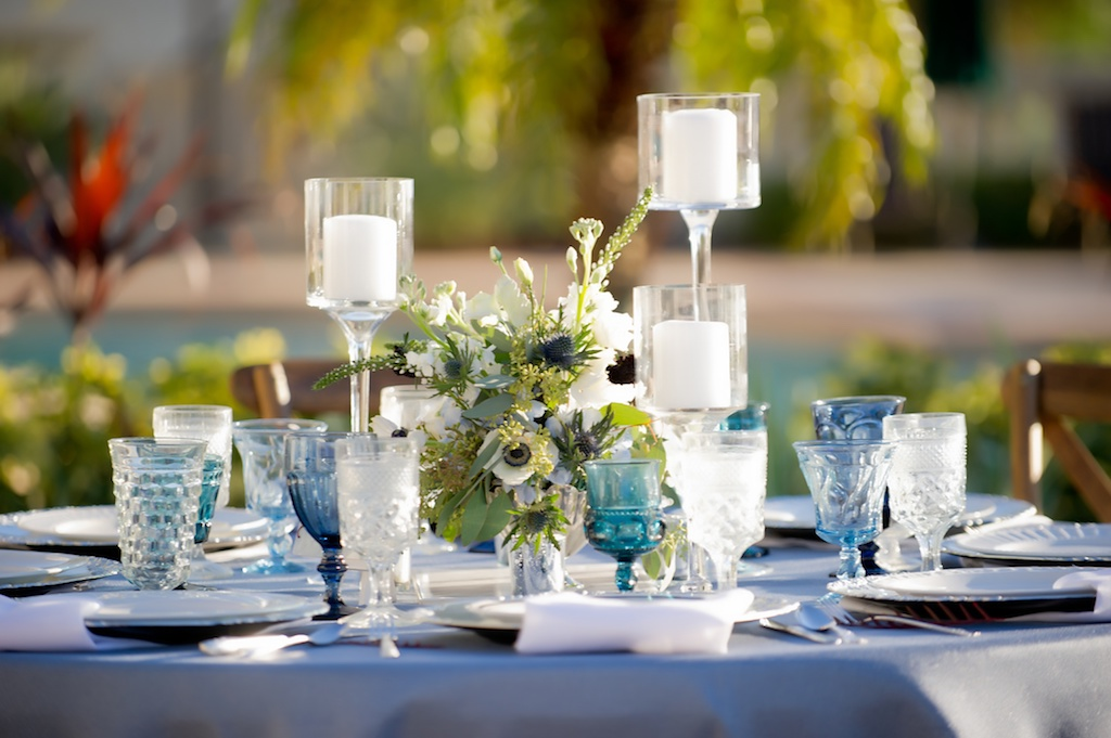 French Countryside Outdoor Wedding Reception Table Decor with Light Blue Linen, Blue Colored Drinking Glasses, Low White Anemone with Greenery and Red Rose Centerpiece, and Pillar Candles in Tall Glass Candleholders, with Stylish Pink Table Number on White Card | Tampa Wedding Planner Kelly Kennedy Weddings & Events | Tampa Bay Wedding Rentals Over The Top Linens and Events | Waterfront Tampa Wedding Reception Venue The Westshore Yacht Club