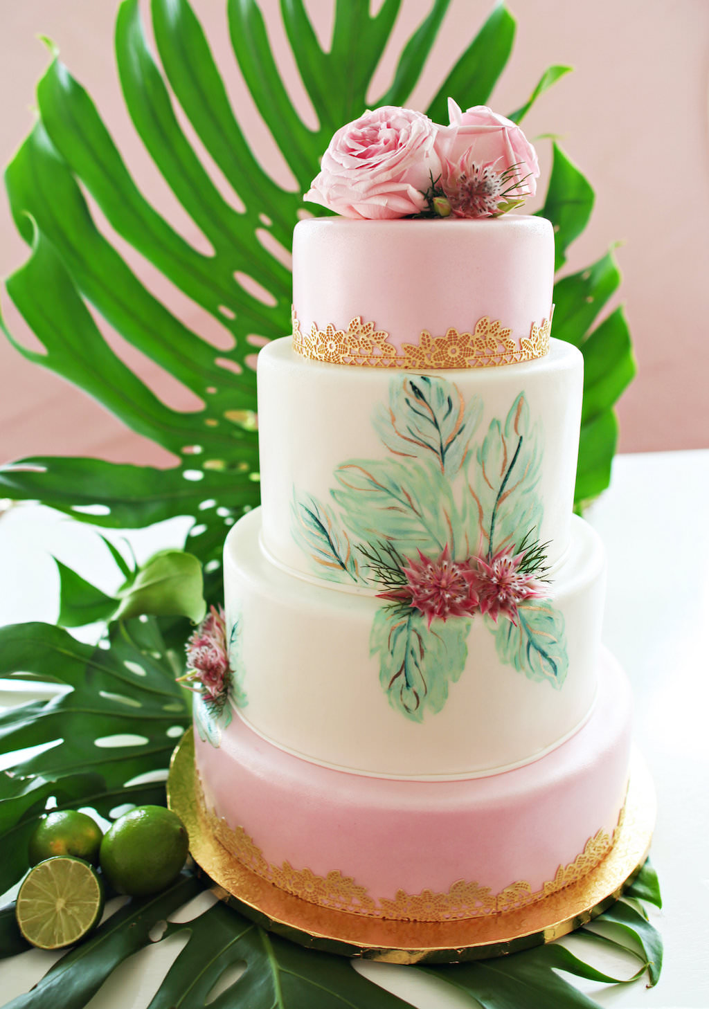 Four Tiered Tropical Havana Inspired Wedding Cake with PInk Icing, Painted Leaf Details and Pink Roses and Gold Floral Details, on Gold Cakestand with Monsterra Palm Frond and Limes