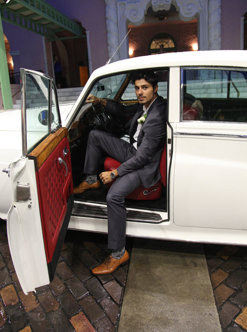 Groom Wedding Exit Portrait in Classic Vintage Car, Wearing Gray Suit with Tan Leather Shoes and WHite Floral Boutonniere