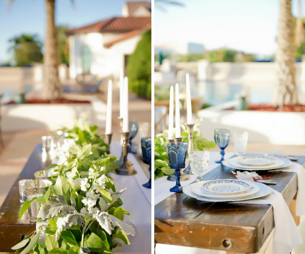French Countryside Outdoor Wedding Reception Sweetheart Table with White Linen Runner and Greenery Garland Centerpiece, Tapered Candles in Silver Candleholders, Blue Colored Drinking Glasses, and Blue and White Painted Porcelain Plates on Silver Chargers with Flatware Wrapped in White Ribbon | Tampa Wedding Planner Kelly Kennedy Weddings and Events