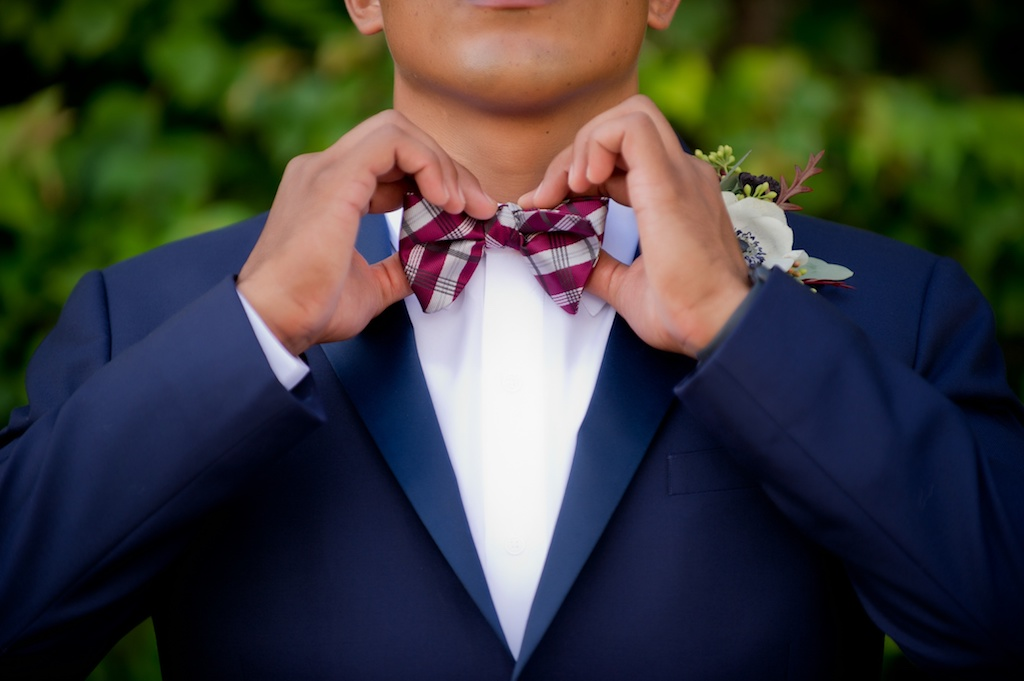Outdoor Garden Groom Portrait In Blue Suit with Burgundy Plaid Bow Tie and Anemone and Greenery Boutonniere | Tampa Bay Wedding Photographer Andi Diamond Photography | Mens Suit Sacinos Formalwear