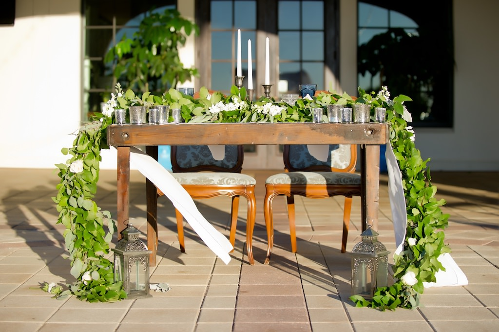 French Countryside Outdoor Wedding Reception Sweetheart Table with Vintage Wooden Chairs, Long White Runner with Greenery Garland Centerpiece, and Blue Colored Drinking Glasses | Tampa Wedding Planner Kelly Kennedy Weddings & Events | Tampa Bay Waterfront Wedding Venue The Westshore Yacht Club