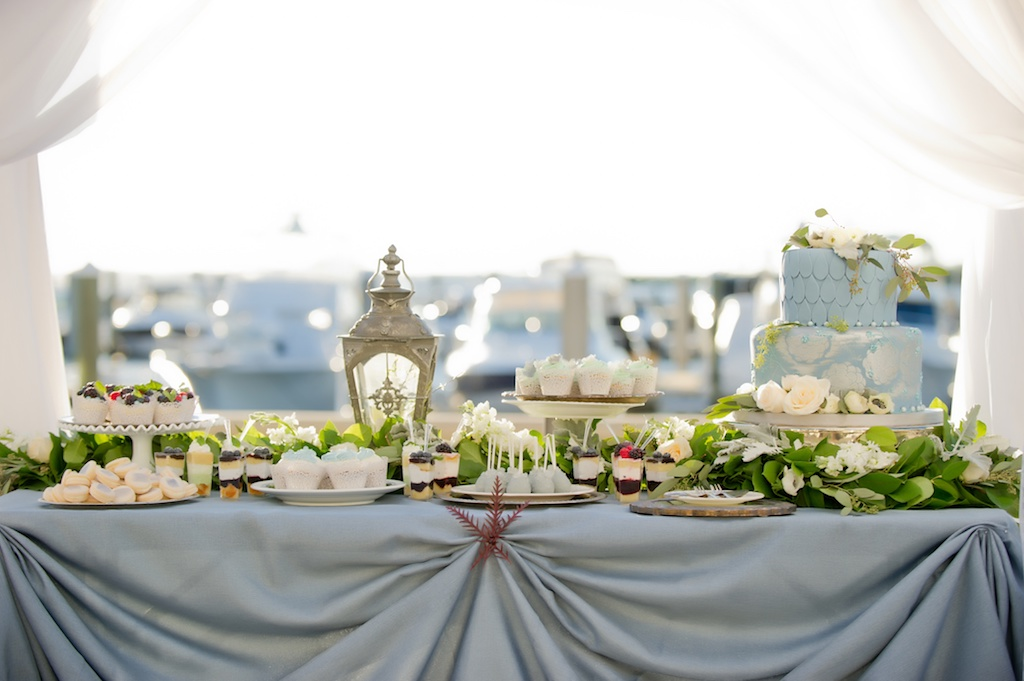 French Countryside Inspired Outdoor Waterfront Wedding Reception Dessert Table with Two Tiered Hand Painted Round Blue Wedding Cake, Cupcakes, Cake Pops, and Parfait Shooters on Silver and Ceramic Cake Trays with Greenery Garland Under White Draping | Tampa Wedding Cake and Desserts Alessi Bakery | Tampa Bay Wedding Planner Kelly Kennedy Weddings & Events | Outdoor Waterfront Tampa Wedding Venue Westshore Yacht Club