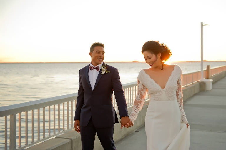 Waterfront Sunset Bride and Groom Wedding Portrait, Groom with Red and White Plaid Bowtie and Blue Suit, Bride in V Neck Lace Long Sleeve Daalarna Couture Wedding Dress | Tampa Wedding Photographer Andi Diamond Photography
