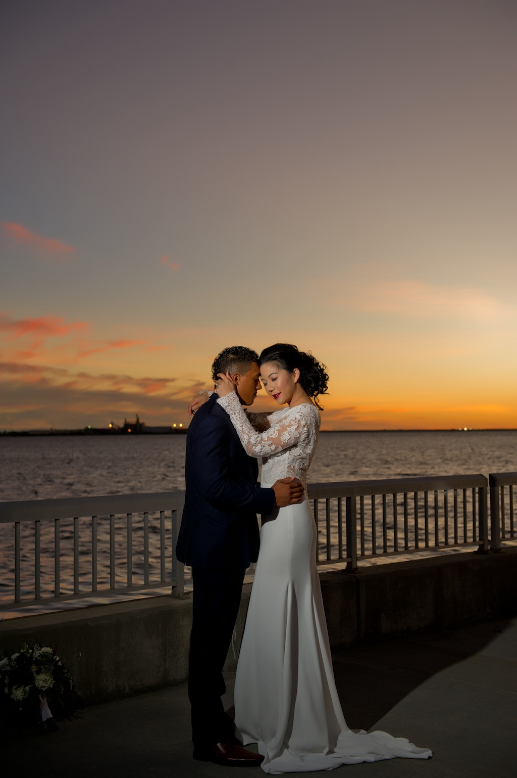 Waterfront Sunset Bride and Groom Wedding Portrait, Groom with Red and White Plaid Bowtie and Blue Suit, Bride in V Neck Lace Long Sleeve Daalarna Couture Wedding Dress | Tampa Wedding Photographer Andi Diamond Photography | Tampa Bridal Wedding Dress Shop The Bride Tampa