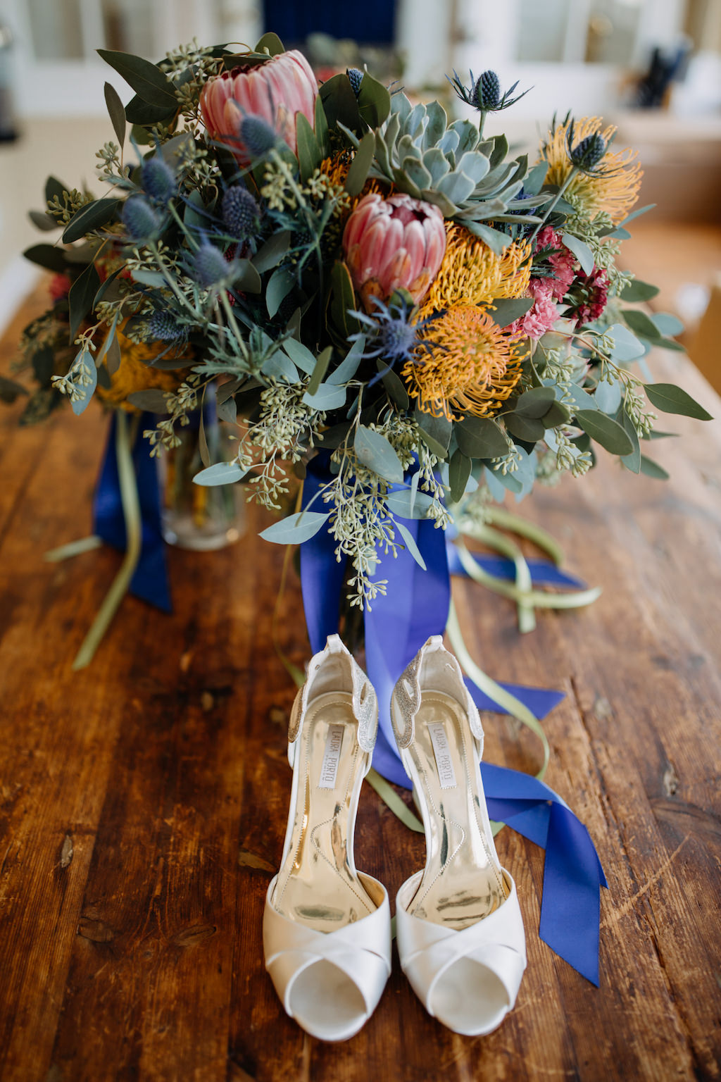 Orange, Red, and Sage Greenery and Succulent Bridal Bouquet with Blue and Green Ribbon and Peep Toe Laura Porto Wedding Shoes