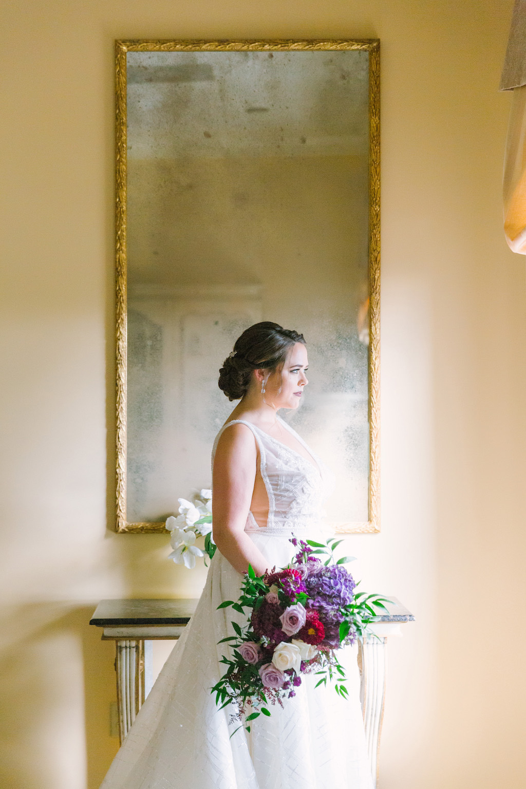 Indoor Bridal Portrait in Calla Blanche V Neck Lace Wedding Dress, with Purple, Magenta, and White Bouquet with Greenery
