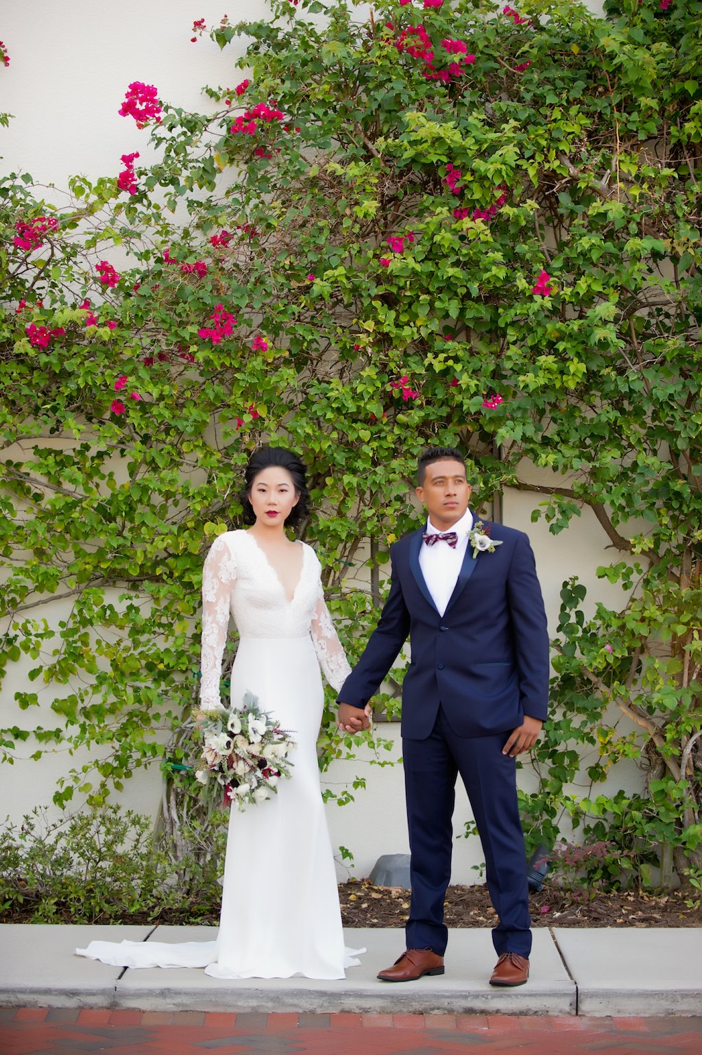 Outdoor Garden Bride and Groom Wedding Portrait, Bride in Long Sleeve V Neck Lace Daalarna Couture Wedding Dress from The Bride Tampa, with Anemone and Greenery Bouquet, Groom in Blue Suit with Pink Bow Tie | Tampa Bay Wedding Photographer Andi Diamond Photography | Tampa Wedding Venue Westshore Yacht Club | Mens Suit Sacinos Formalwear