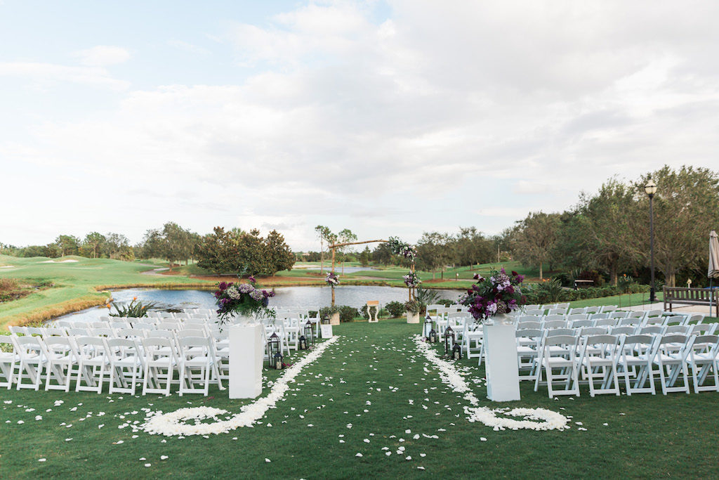 Whimsical Outdoor Violet Wedding Ceremony with Large Purple Floral with Greenery Arrangements on Pillars with White Petal Aisle, White Folding Chairs, and Bamboo Ceremony Arch | Sarasota Country Club Wedding Venue Lakewood Ranch Golf & Country Club