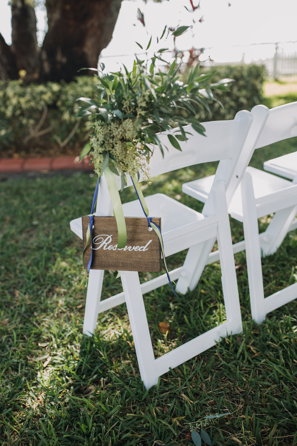 Outdoor Garden Wedding Ceremony White Folding Chair with Wooden Painted Reserved Sign with Greenery Florals and Sage Green and Cobalt Blue Ribbon