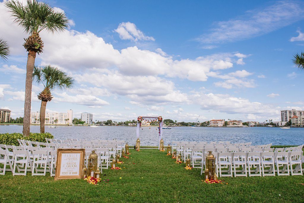 Outdoor Waterfront Jewel Tone Whimsical Wedding Ceremony with Gold Lanterns and Yellow and Red Rose Petals with Folding White Chairs and White Drapery and Floral Ceremony Arch | Tampa Bay Outdoor Wedding Ceremony Venue Clearwater Beach Recreation Center | Planner Special Moments Event Planning