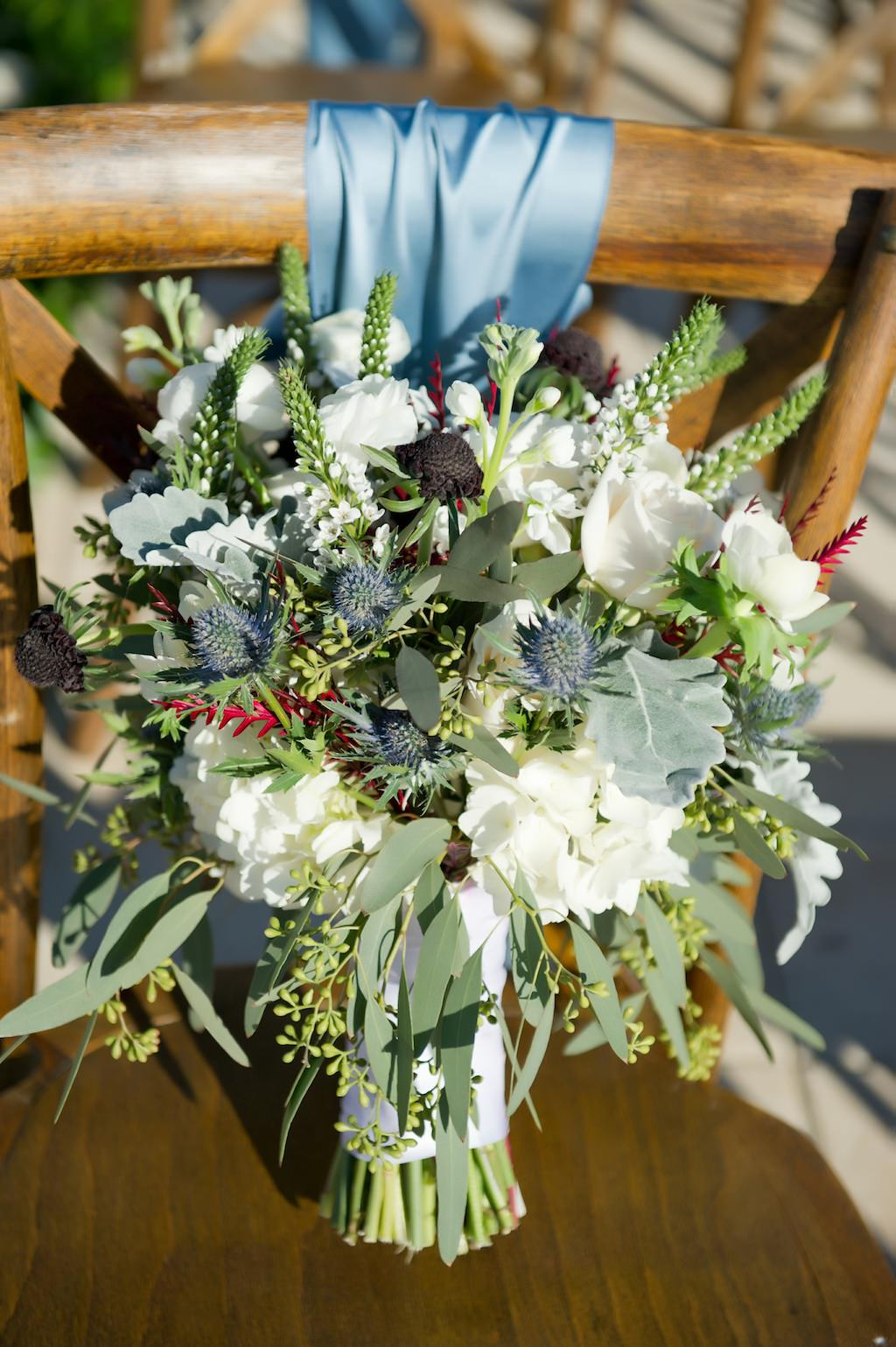 Wild Greenery and White Floral with Thistle Wedding Bouquet on Wooden Cross Back Chair with Blue Ribbon