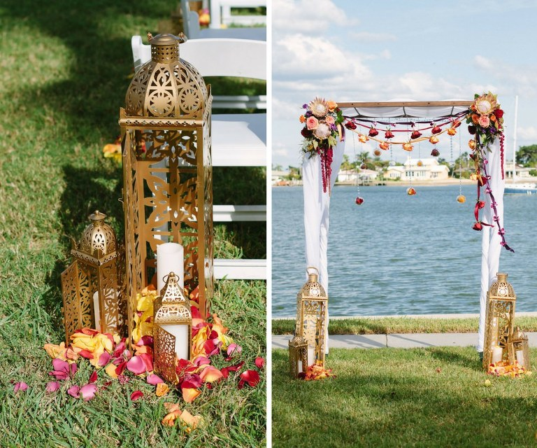 Outdoor Waterfront Whimsical Jewel Tone Wedding Ceremony Decor with Tall Moroccan Lanterns and Yellow and Red Flower Petals, and Ceremony Arch with Red and Gold Rose Garlands with Ribbon and White Draping | Tampa Bay Wedding Planner Special Moments Event Planning