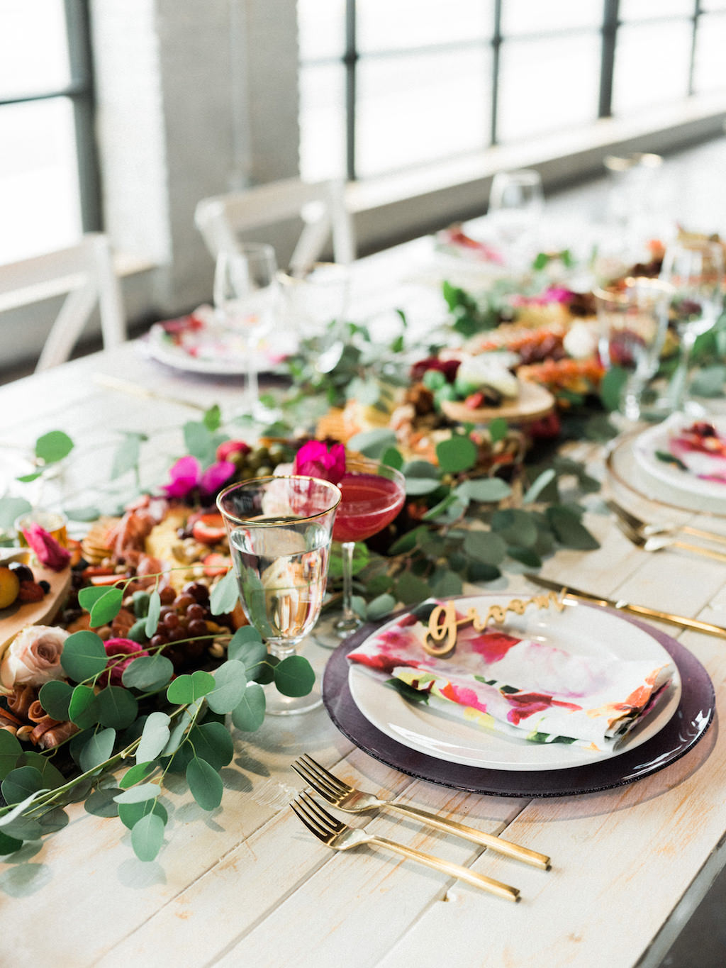 Modern Fuchsia Wedding Reception Table with Charcuterie Board with Greenery, Wooden Table, White Cross Back Chairs, Gold Flatware   Lakeland Florida Wedding Caterer Tastes of Tampa Bay   Chair Rentals A Chair Affair   Venue Haus 820