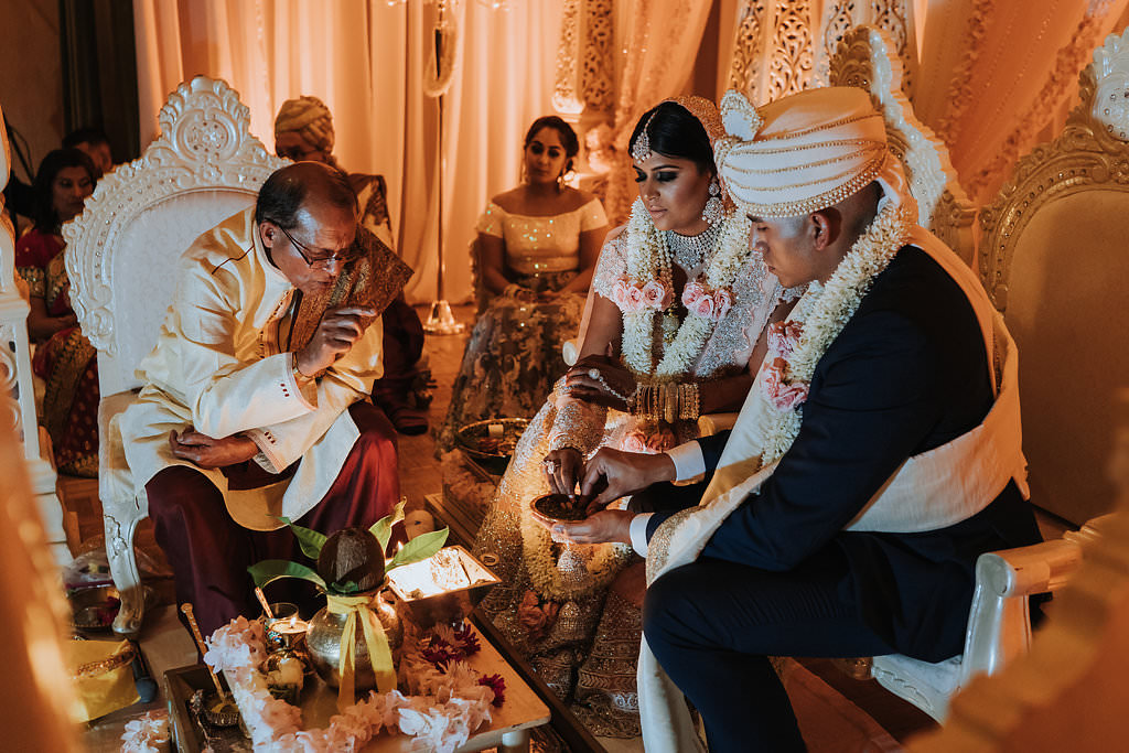 Regal and Romantic Traditional Hindu Indian Wedding Ceremony Bride and Groom Portrait with Gold Uplighting and Blush Pink Draping Behind the Mandap   Tampa Bay Wedding Venue Safety Harbor Resort and Spa   Planner Glitz Events   Photographer Grind and Press Photography