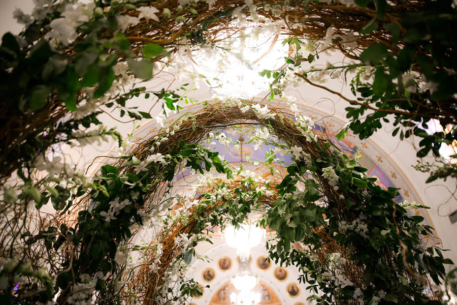 Traditional Greek Wedding Ceremony Interior Decor with Enchanted Garden Wild Branch Arch with White Florals and Greenery   Tarpon Springs Traditional Wedding Venue St. Nicholas Greek Orthodox