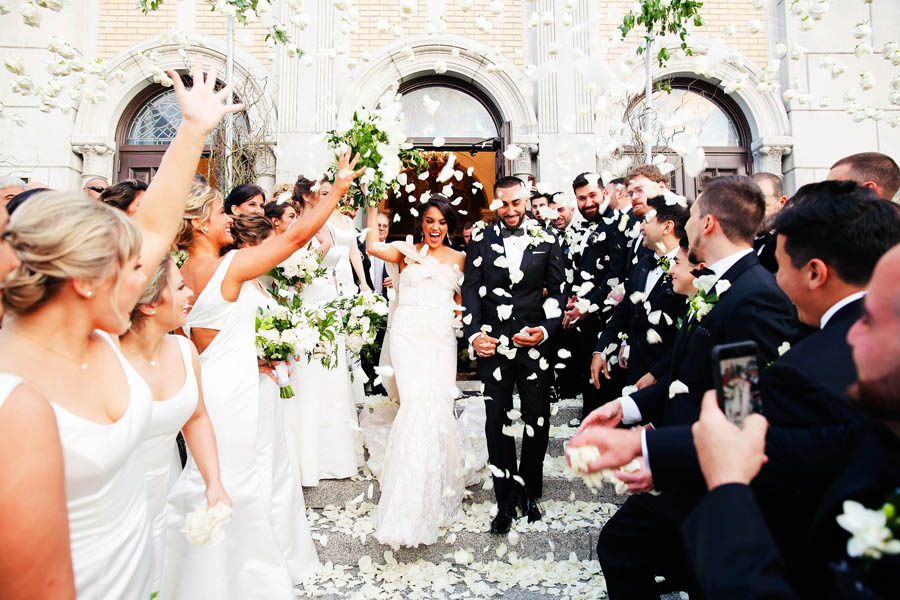 Greek Wedding Ceremony Exit Portrait with Greenery and White Petals, Bridesmaids in Floorlength White Dresses, Groomsmen in Black Tuxes with White Boutonniere