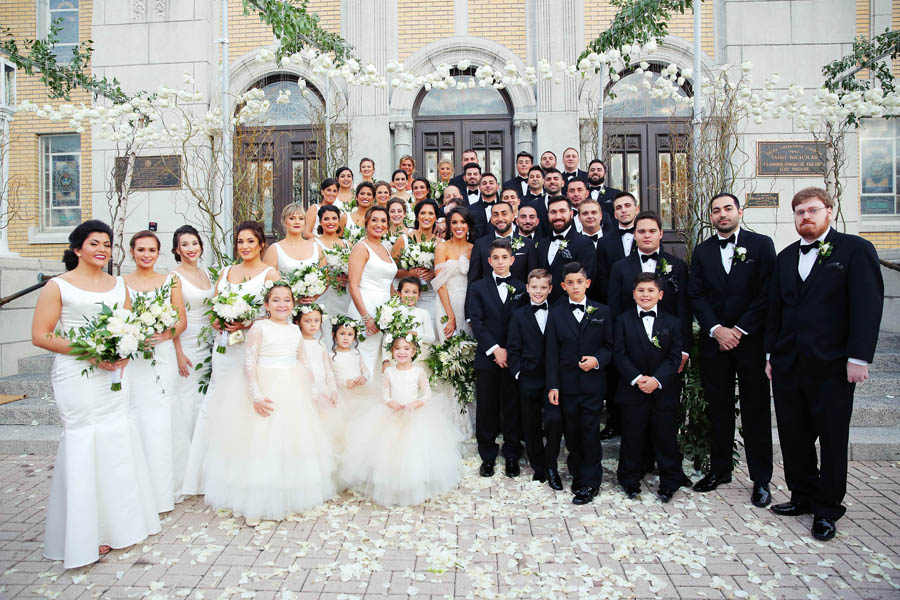 Outdoor Wedding Party Portrait, Bridesmaids in Floorlength White Hayley Paige Bella Bridesmaids Dresses, Groomsen in Black Tuxedos with White and Greenery Boutonniere, Flower Girls in Blush Pink Dresses with Layered Skirts, under hanging White Flowers, Greenery, and Wild Branch Arches   Tarpon Springs Venue St Nicholas Greek Orthodox Church