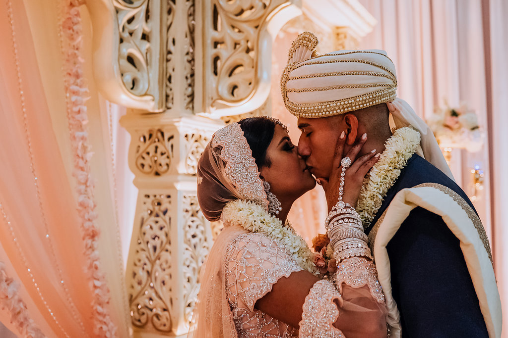 Regal and Romantic Traditional Hindu Indian Wedding Ceremony Bride and Groom First Kiss Portrait with Gold Uplighting and Blush Pink Draping Behind the Mandap   Tampa Bay Wedding Venue Safety Harbor Resort and Spa   Planner Glitz Events   Photographer Grind and Press Photography