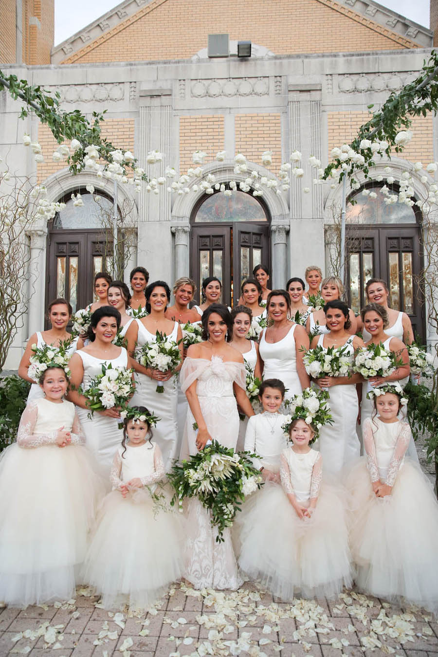 Outdoor Bridal Party Portrait, Bridesmaids in Floorlength White Hayley Paige Bella Bridesmaids Dresses, Flower Girls in Blush Pink Dresses with Layered Skirts, under hanging White Flowers, Greenery, and Wild Branch Arches   Tarpon Springs Wedding Venue St Nicholas Greek Orthodox Church