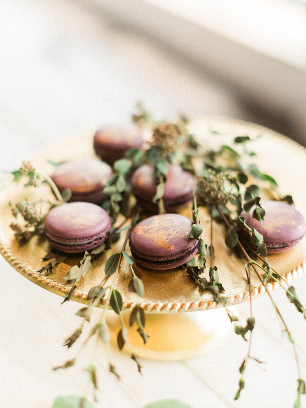 Modern Wedding Dessert Gold and Purple Macaroons on Gold Cake Stand with dried greenery