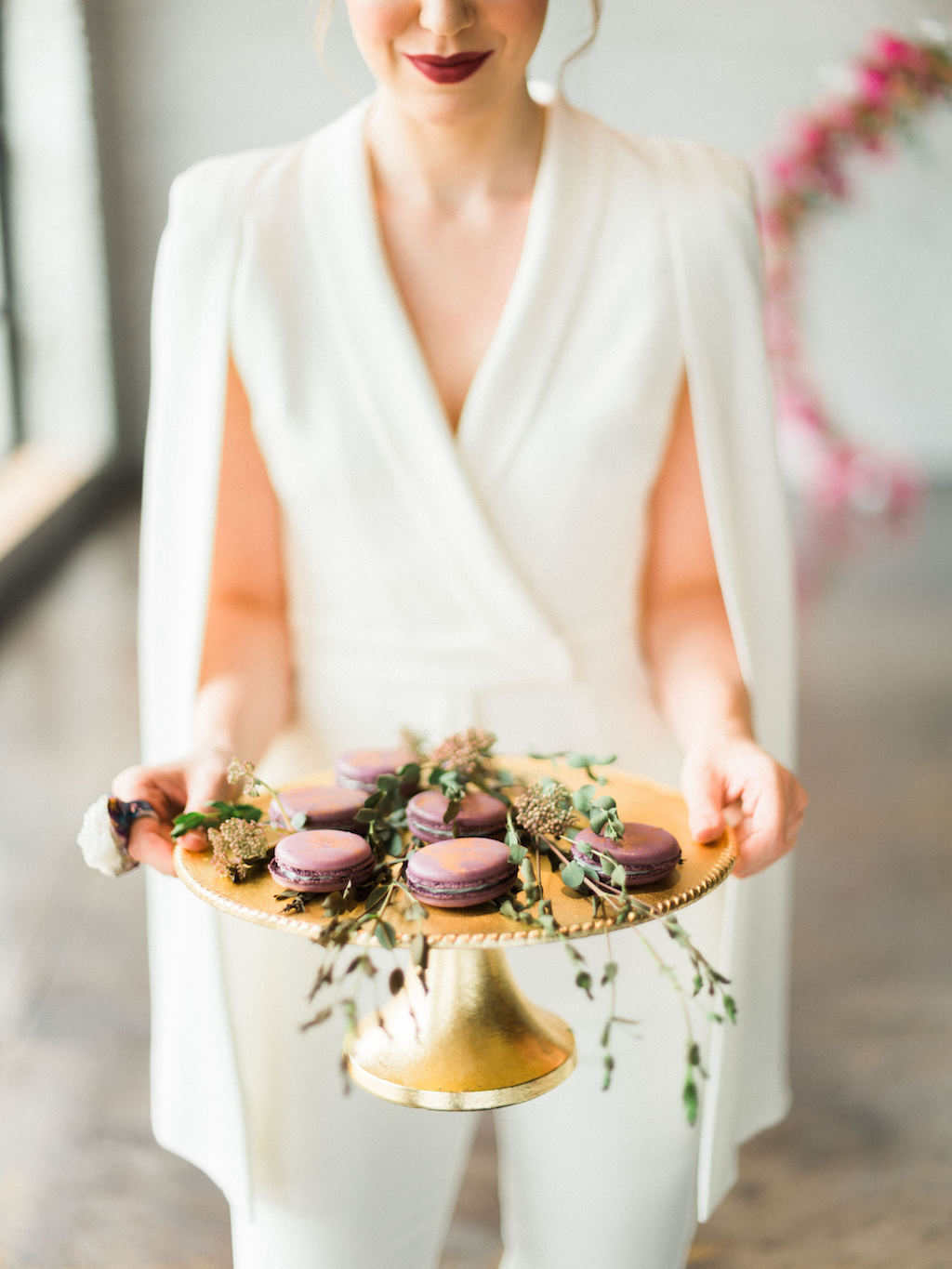 Bride in Lavish Alice White Jumpsuit with Cape with Modern Wedding Gold and Purple Macaroons on Gold Cake Stand with dried greenery