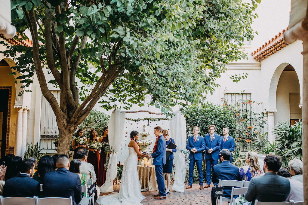 Outdoor Garden Modern Indian Wedding Ceremony Portrait Decor with Hanging Blush, Red, and Orange Rose Garland and White Draped Arch, Groom and Groomsmen in Blue Suits, Bridesmaids in Red Dresses | Tampa Bay Wedding Venue St Petersburg Museum of Fine Arts | Wedding Photography Rad Red Creative | Menswear Sacino's Formalwear