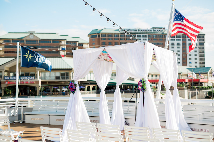 Outdoor Waterfront Wedding Ceremony with White Folding Chairs, White Draped Chuppah Wedding Arch with Purple, Blue, White, and Red Flowers | Tampa Bay Nautical Wedding Venue Yacht StarShip