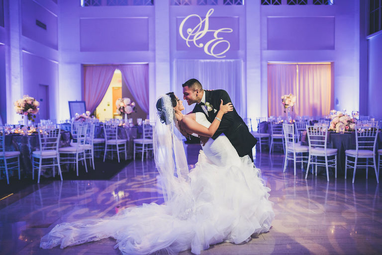 Modern Violet Wedding Reception Bride and Groom First Dance Portrait, Bride in Layered Mermaid Strapless Pronovias Dress, with White Chiavari Chairs and White and Pink Tall Centerpieces | Downtown Tampa Wedding Venue The Vault | Planner Special Moments Event Planning | Custom Monogram Projection and Purple Uplighting Nature Coast Entertainment | Tampa Bay Wedding Shop Isabel O'Neil Bridal Collection